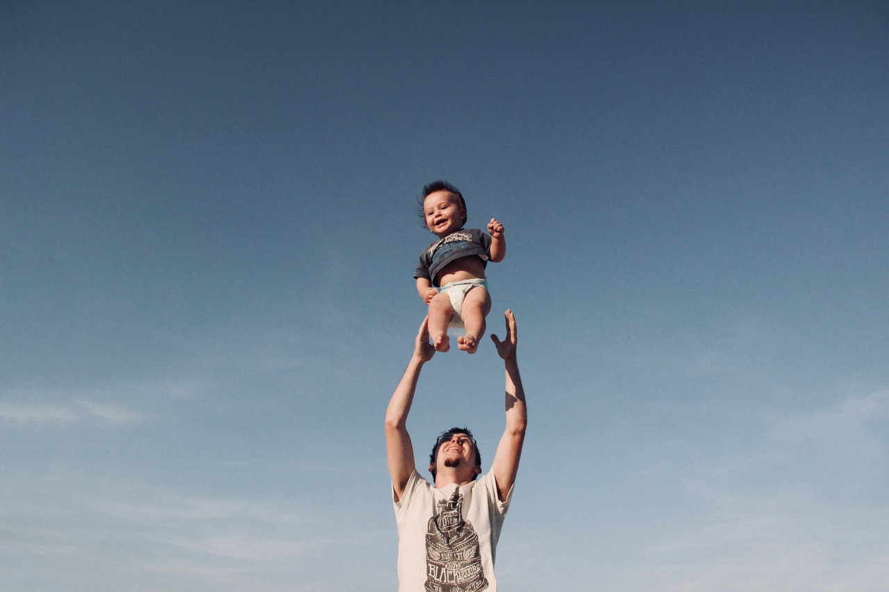 A dad throwing his son in the air to catch it